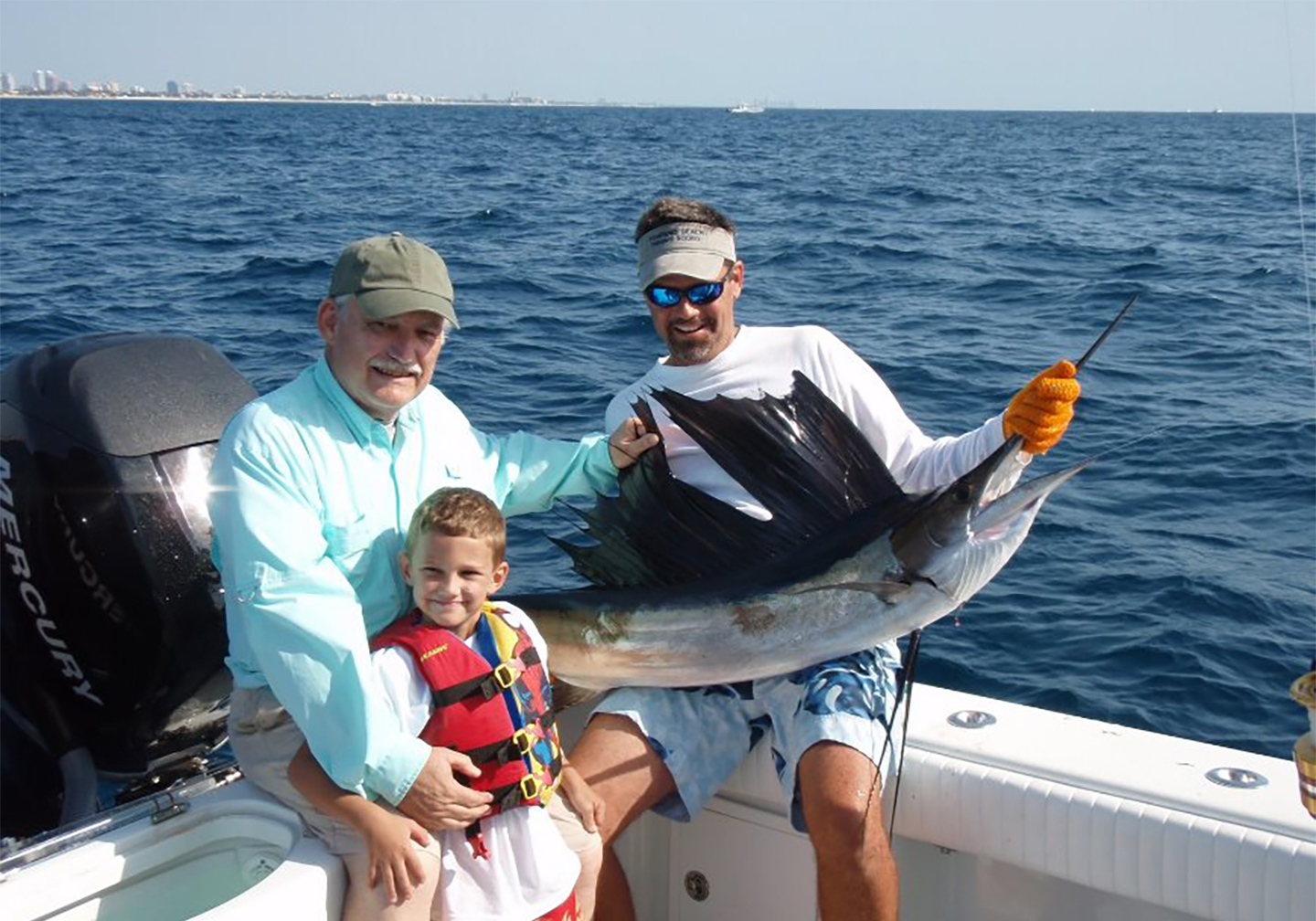 A grandpa with his grandson next to a Sailfish caught while Fort Lauderdale drift fishing.