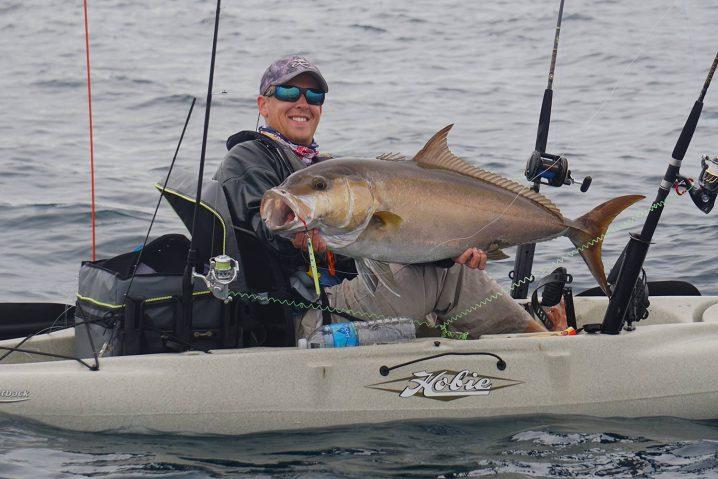 A man on a fishing kayak holding an amberjack fish