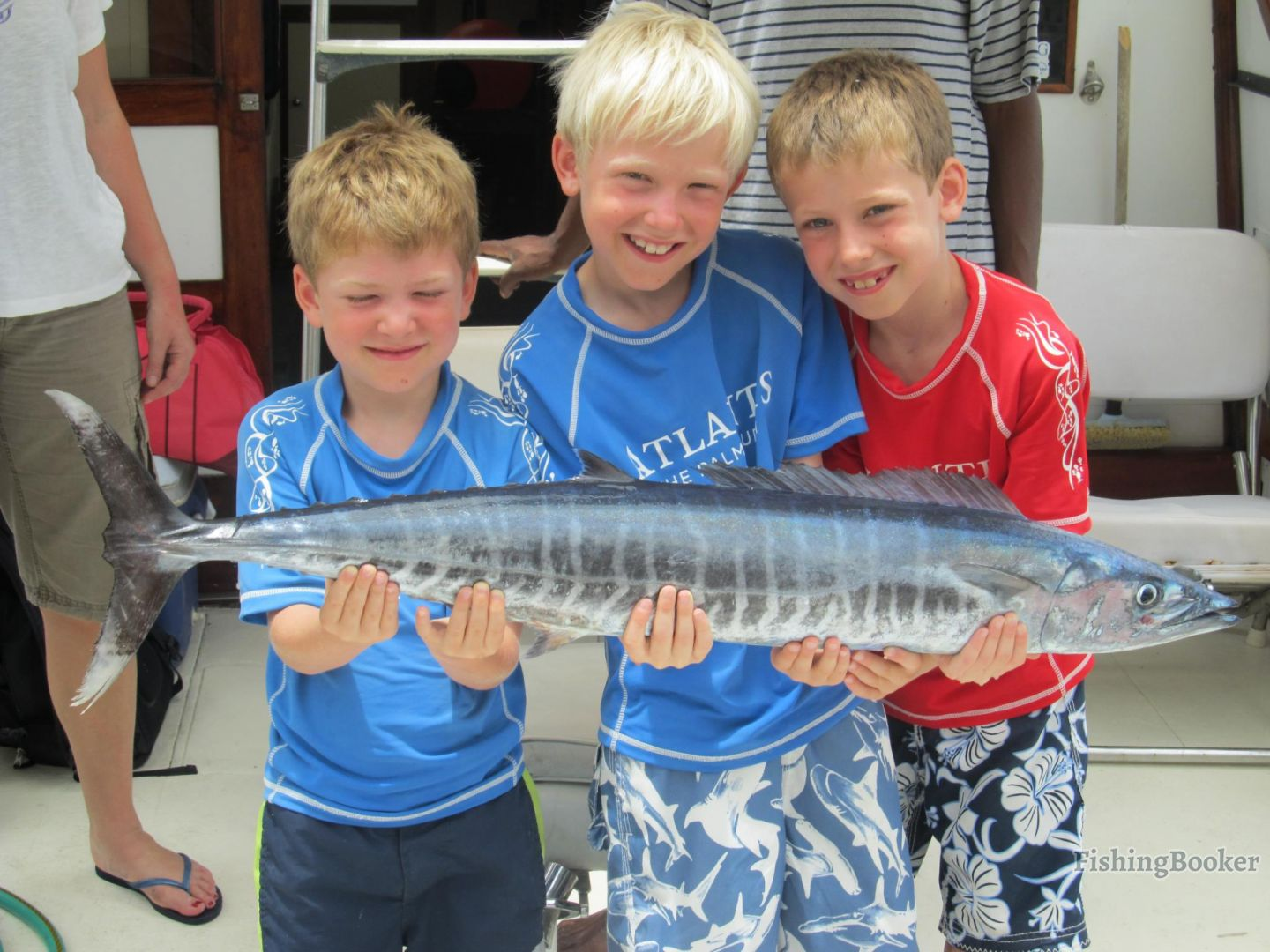 Three young boys holding a Wahoo