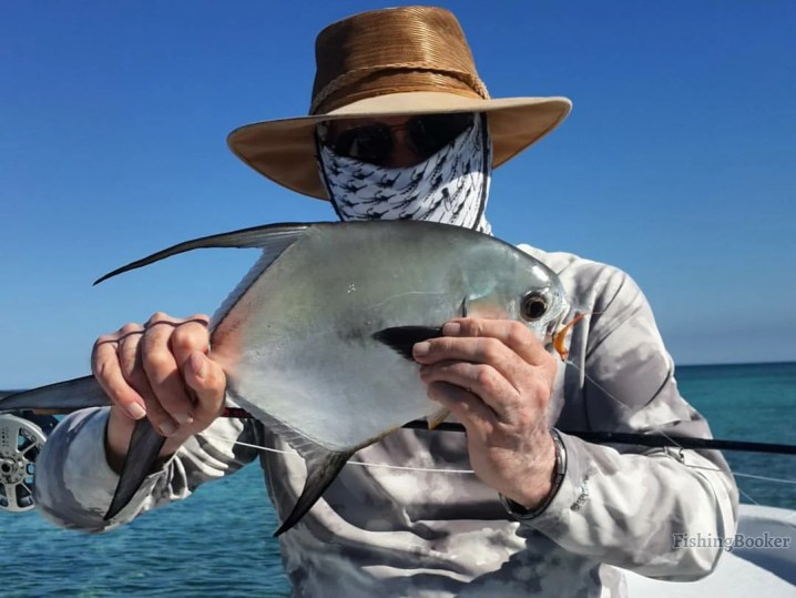 An angler holding a Permit he caught while fishing in Belize