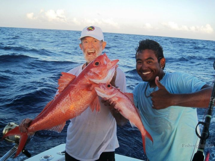Reef fishing in Belize: An angler and a boat mate holding Snapper they caught on their fishing trip