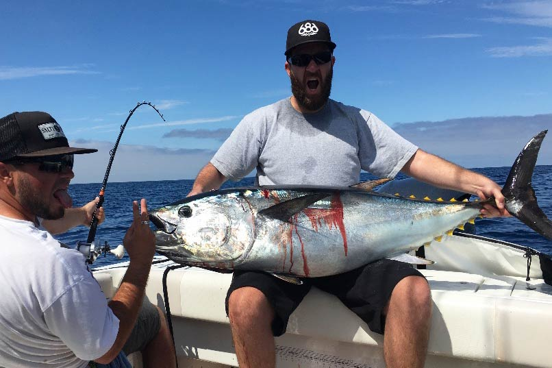 A pair of enthusiast anglers holding a large Bluefin Tuna aboard a charter fishing vessel.