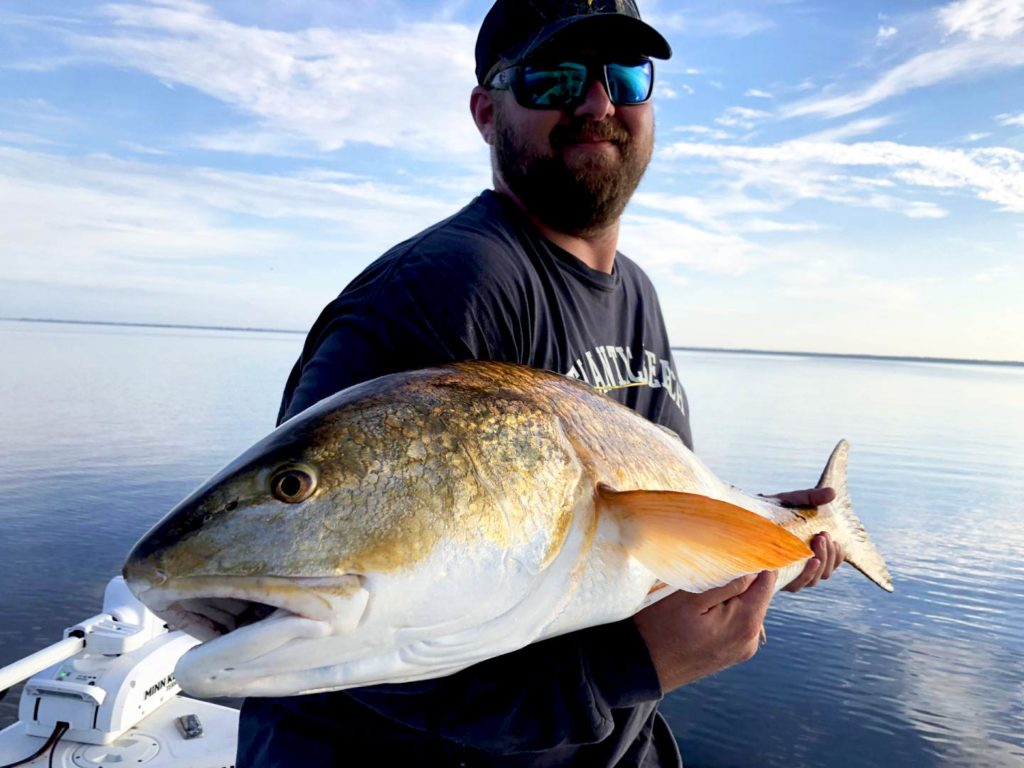 Angler holding a big Redfish