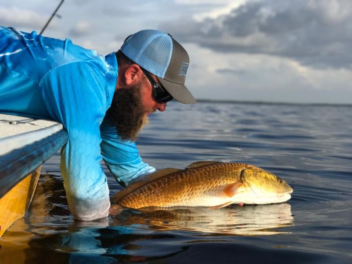 A man in a blue shirt and a cap releasing a Redfish off the side of a boat into the sea