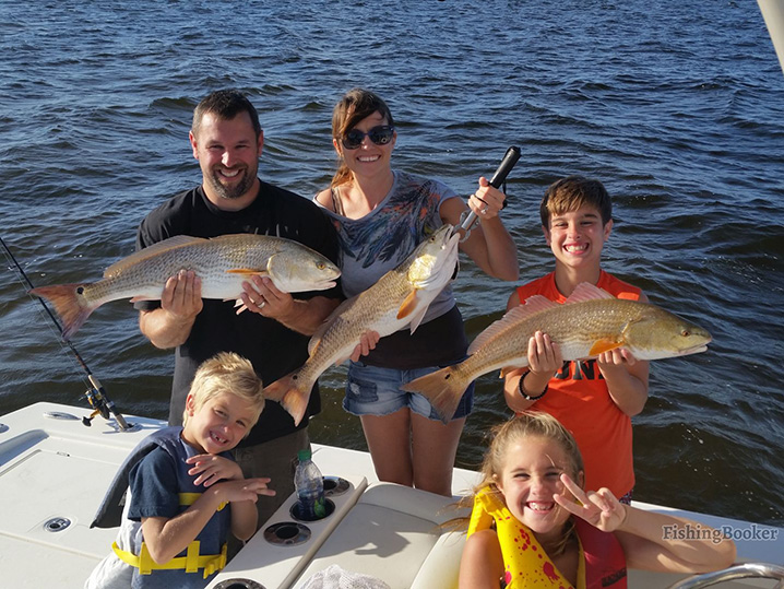 Parents with kids fishing the Chesapeake Bay and holding Redfish.