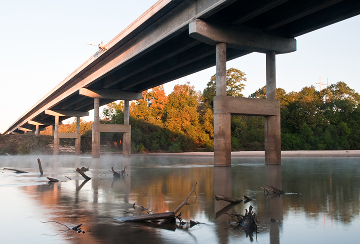 The bridge over the Choctawhatchee River, with drowned trees poking out of the water and trees in the sunlight in the distance