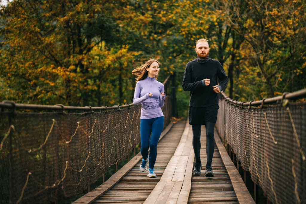 A couple running together over a wooden bridge, with forest behind them.