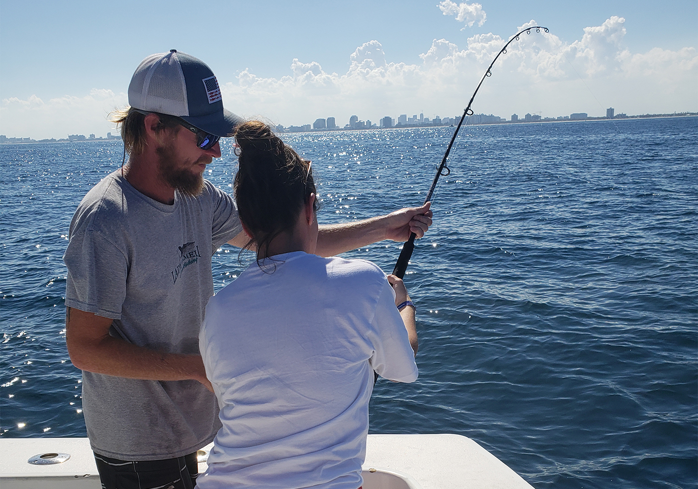 A crew member helping the customer while drift fishing.