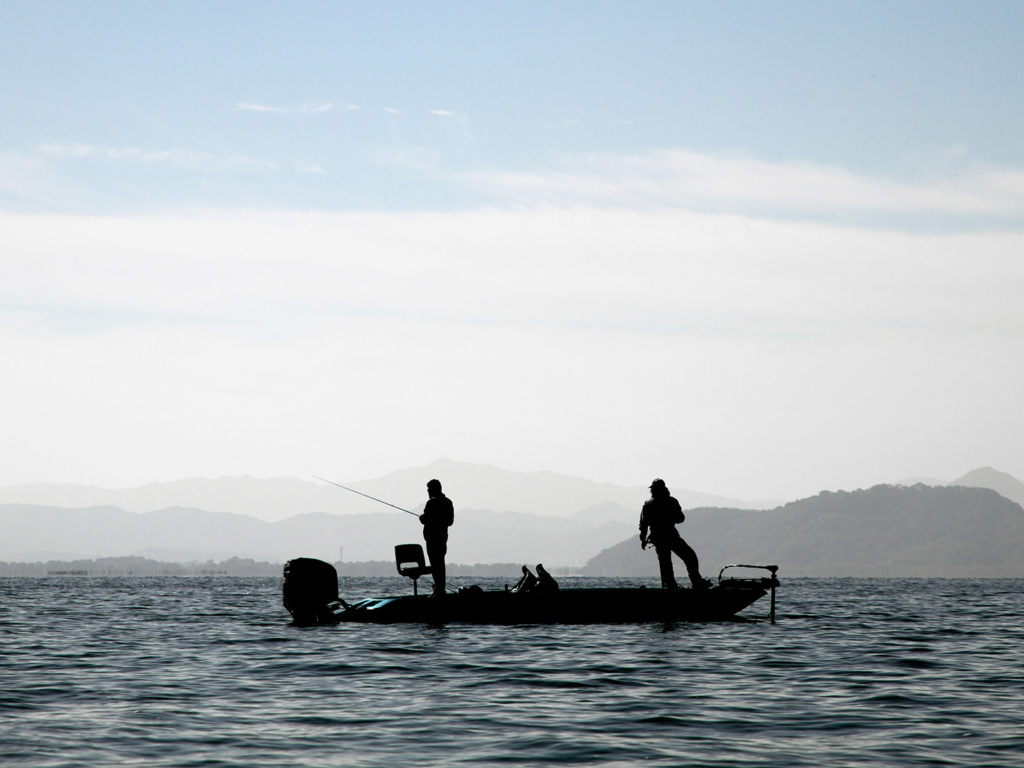 Two men on a Bass fishing boat on a lake. the man at the back is finesse fishing while the man at the front relaxes