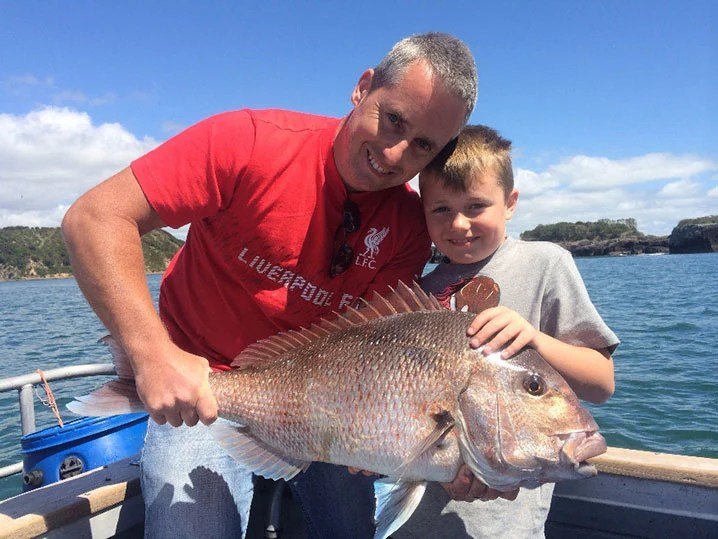 Photo with a good lighting showing a father and son smiling and holding pink snapper during a fishing charter