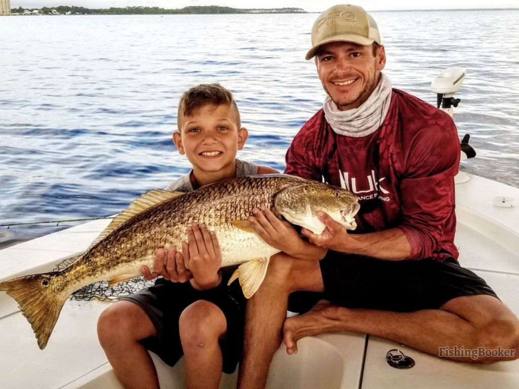 A fishing charter captain and a smiling boy angler holding a Redfish, on a charter boat, with sea in the background