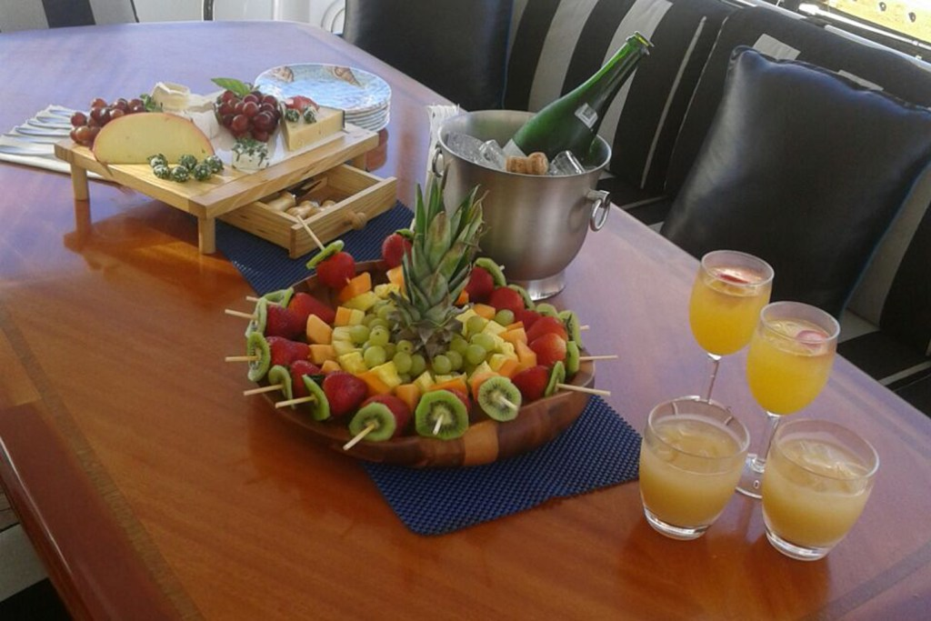A selection of fruit and drinks laid out on a table on a boat.