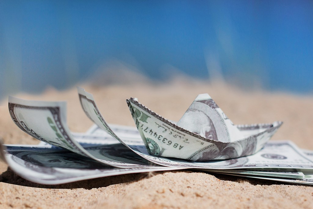 A stack of dollar notes on a beach with a 100 dollar bill folded into a boat. Confusions about money can be the most uncomfortable part of fishing in Spanish.