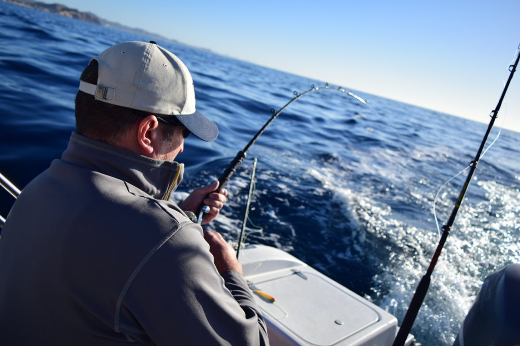 An angler struggling to reel in a big fish on a fishing charter in Latin America.