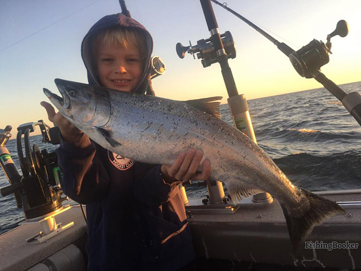 A young boy holding a Salmon which he caught on his family fishing trip in Grand Haven