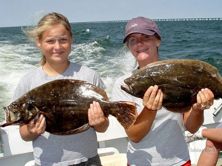 Two young girls holding Flounders they caught on their family fishing trip in Hampton, Virginia.