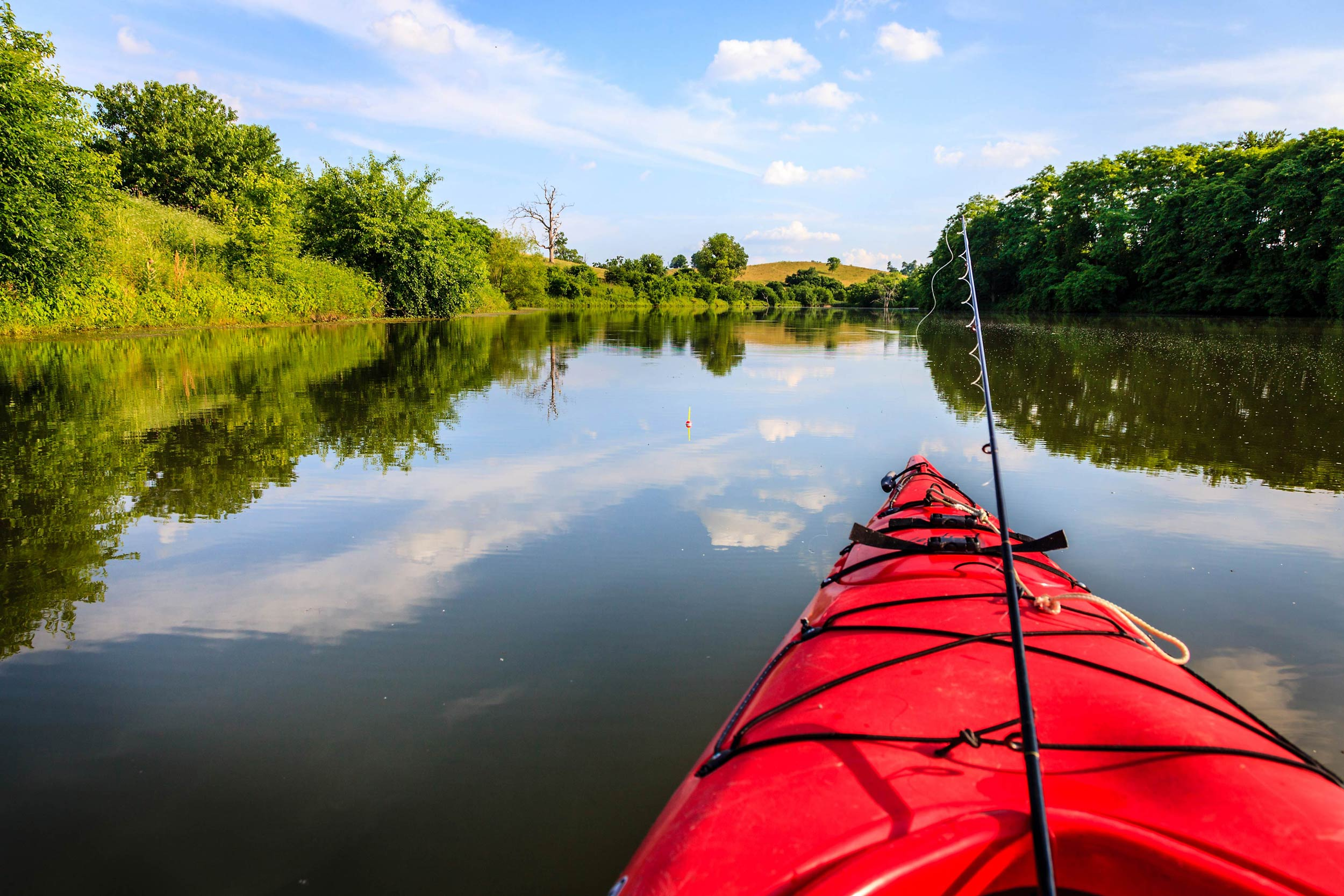 A photo showing the front of a kayak with a fishing rod propped in front and beautiful view