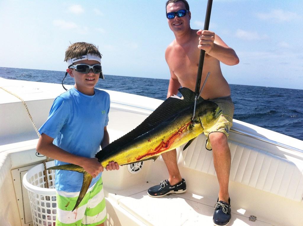 a boy and a young angler holding a mahi mahi on a fishing boat