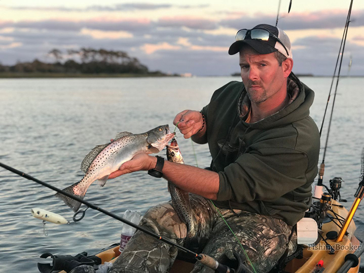 An angler in kayak holding a speckled trout caught while fishing in the outer banks sounds