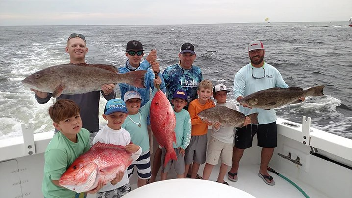Destin party boat fishing: a group of anglers with kids holding Red Snapper and Grouper fishing from a party boat