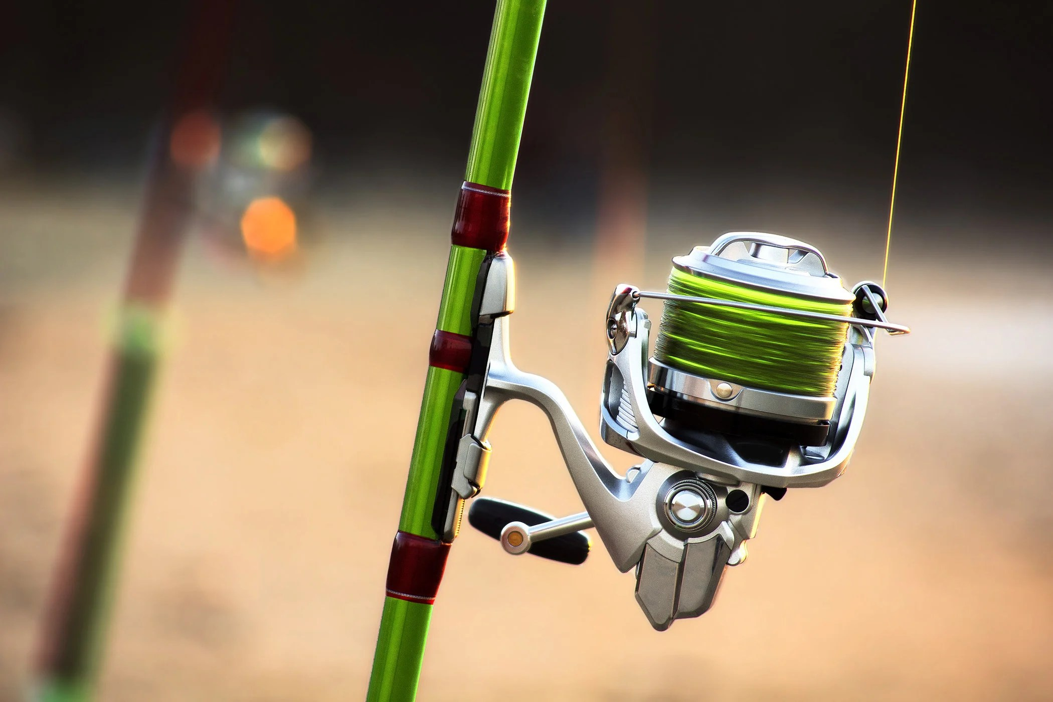 a closeup of a green fishing rod with a spinning reel and a green fishing line