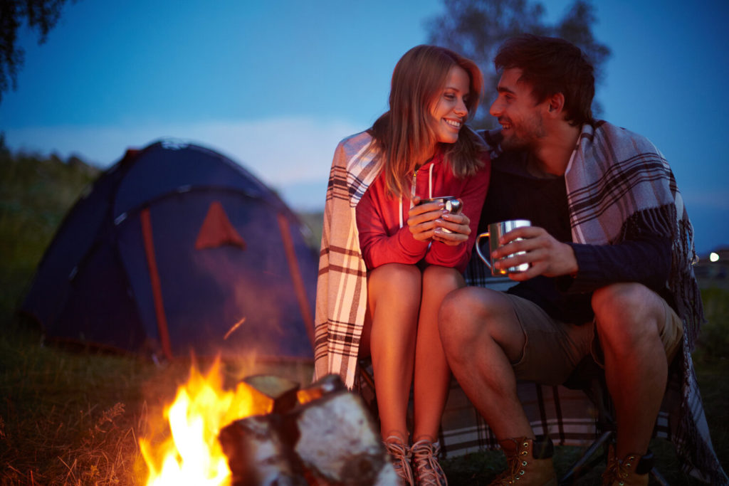 A young couple sitting in front of a tent and bonfire, holding coffee mugs and looking into each other's eyes.