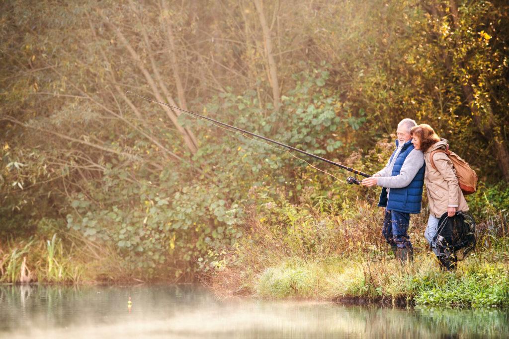 A senior couple fishing together on a lake.