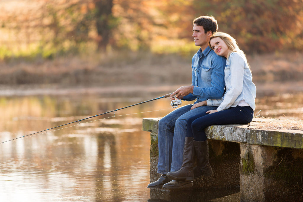 A couple sitting on a dock while the man holds a fishing rod.