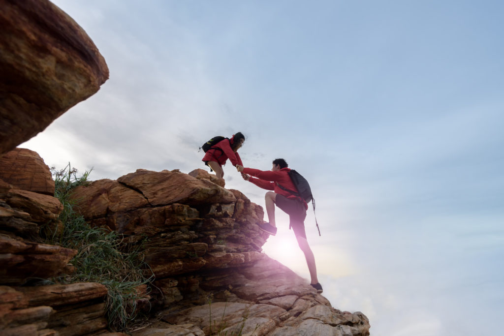 A girl hiker is standing on a top stone and helping out another hiker climb up.
