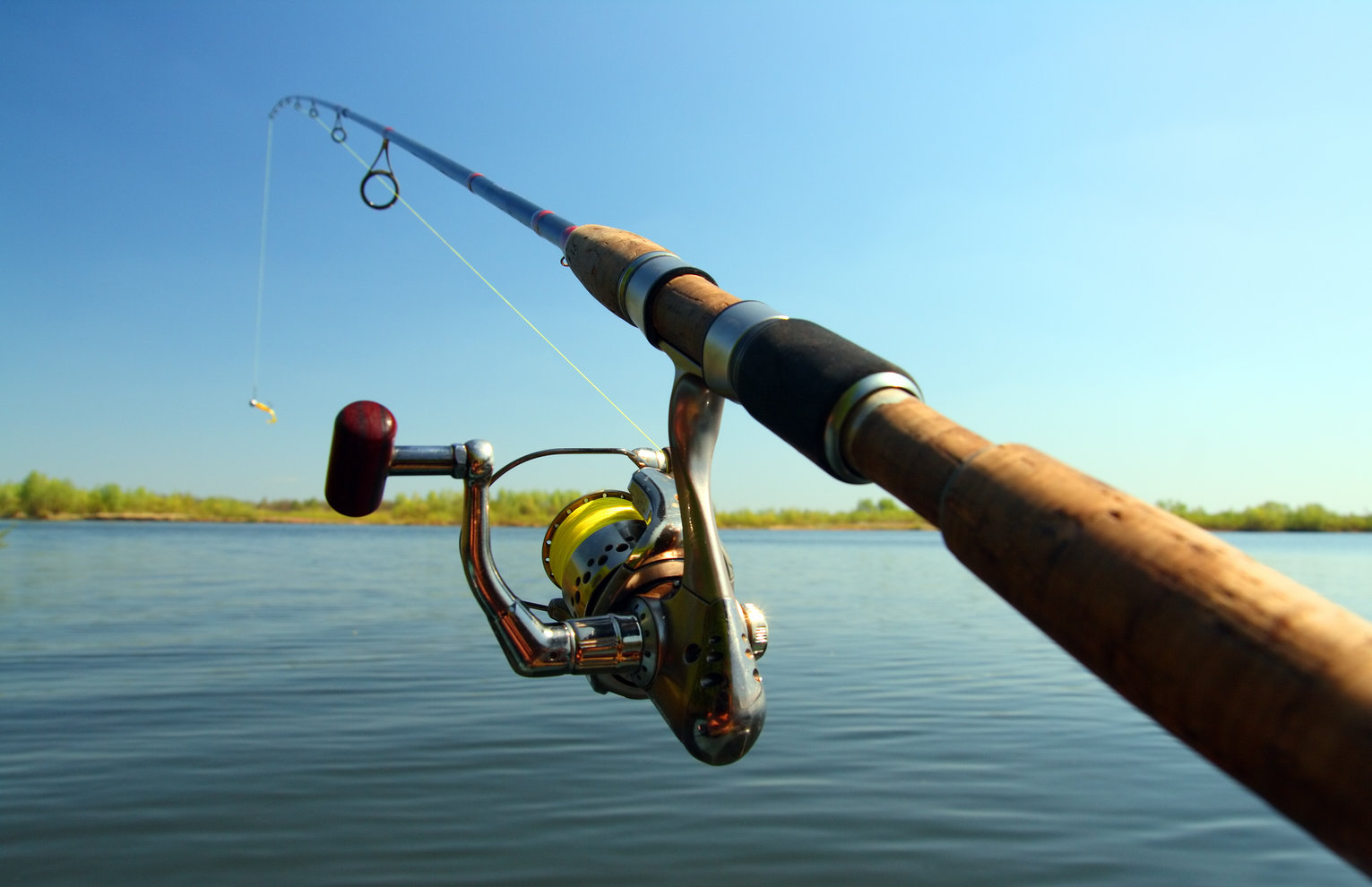 a closeup of a fishing rod with a lake in the background