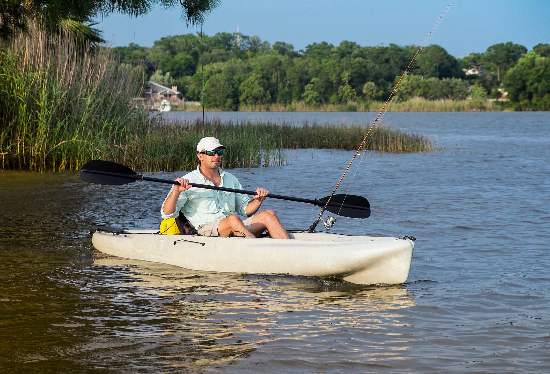 A man in a kayak with a fishing rod on the water rowing