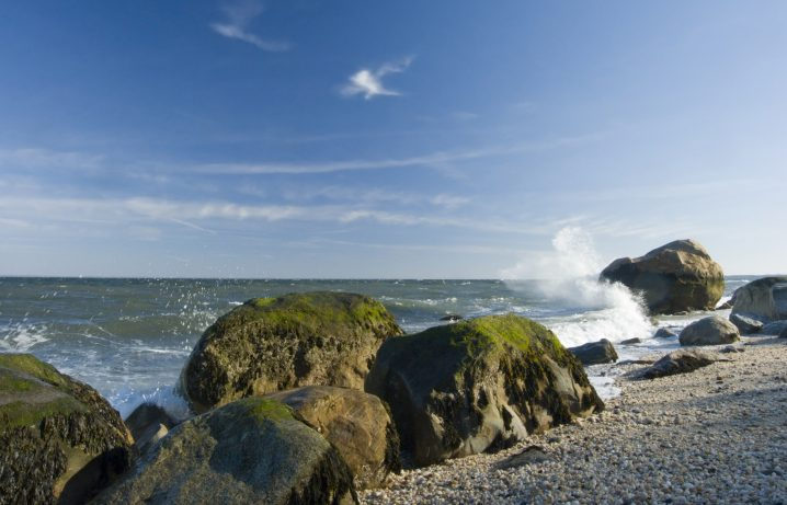 Coastline with waves breaking onto large mossy boulders