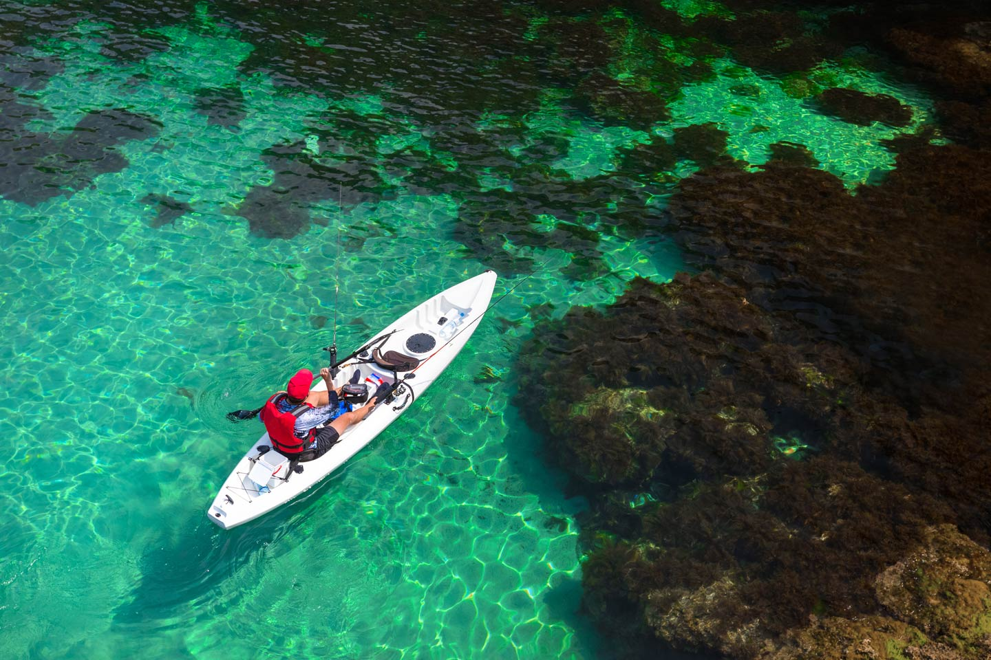 Man fishing on a kayak in the sea with clear turquoise water
