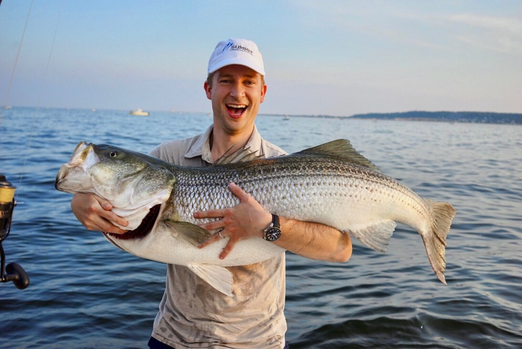 an smiling angler holding a striped bass on a boat