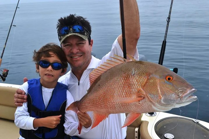 A dad and his son holding a Snapper they caught while fishing reefs out of Tavernier Key.