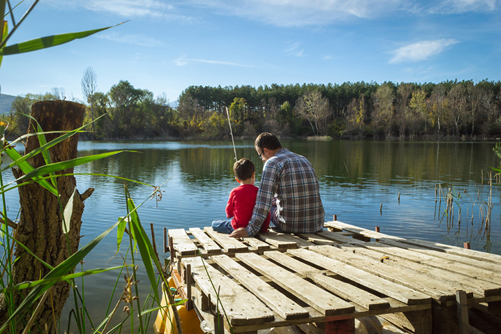 A dad and his son fishing from a pier on Walnut Creek Lake.