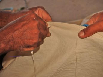 Stitching the sail to the rope mast
