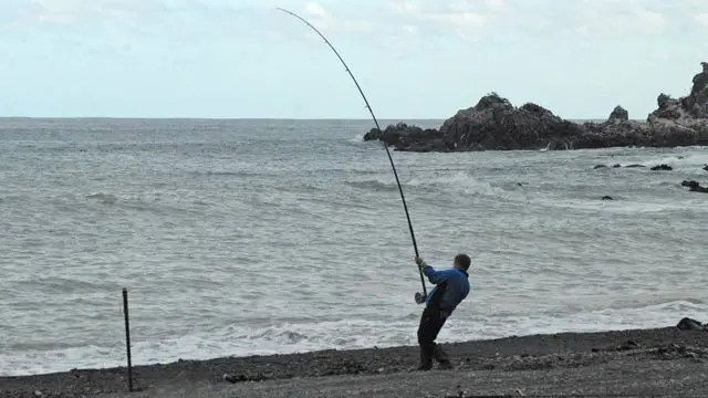 The author with long surf rod. Note that most of the curve is in the top half of the rod. Surfcasting Tips for Beginners New Zealand