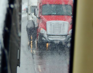Poor trucker chaining up right on the highway. This photo taken in my rear view mirror.