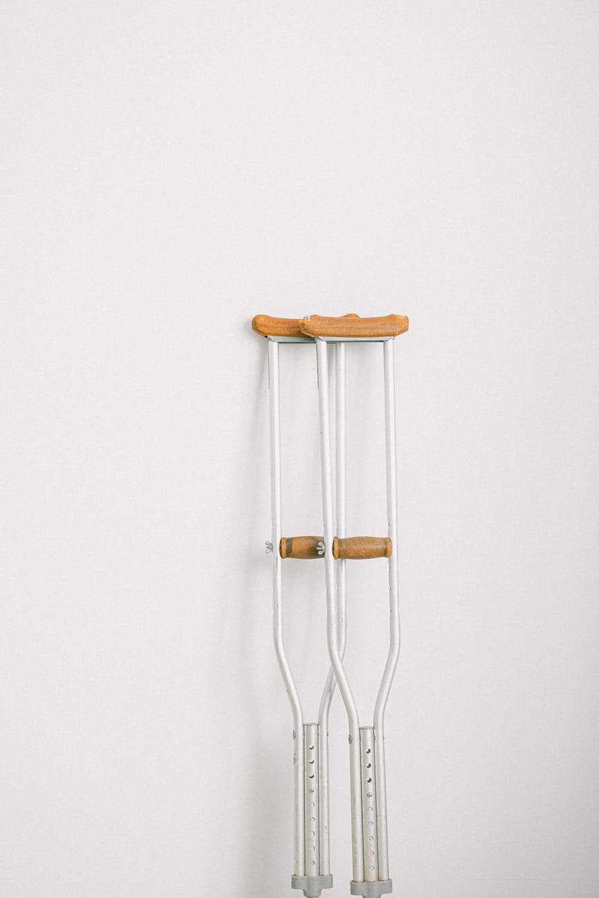 crutches against light white wall