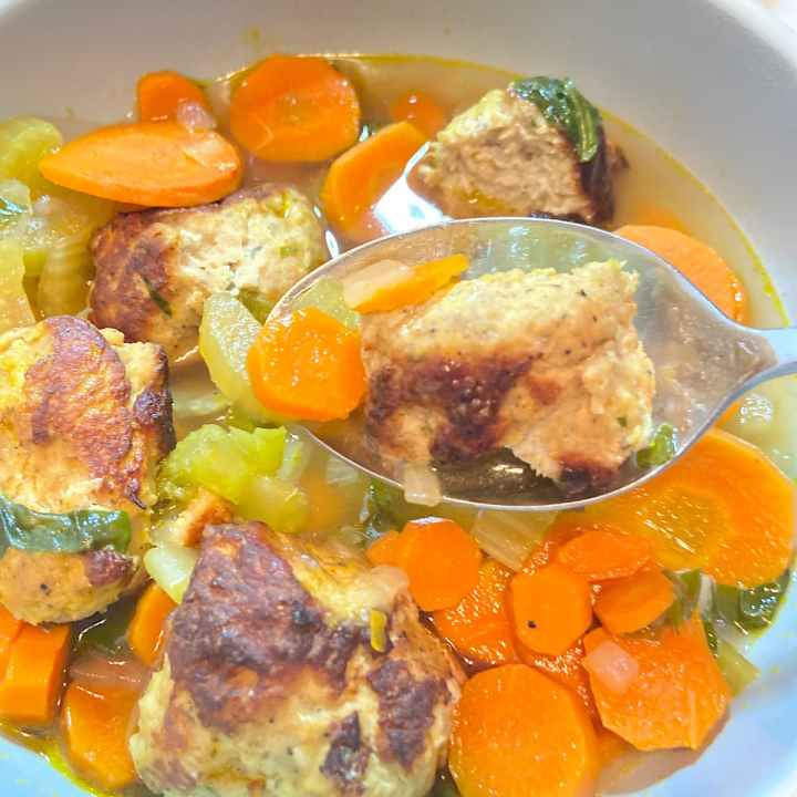a spoonful of turkey meatball and kale soup over a bowl of soup
