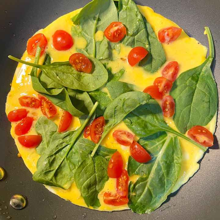 tomatoes and spinach on whisked eggs for vegetable omelet