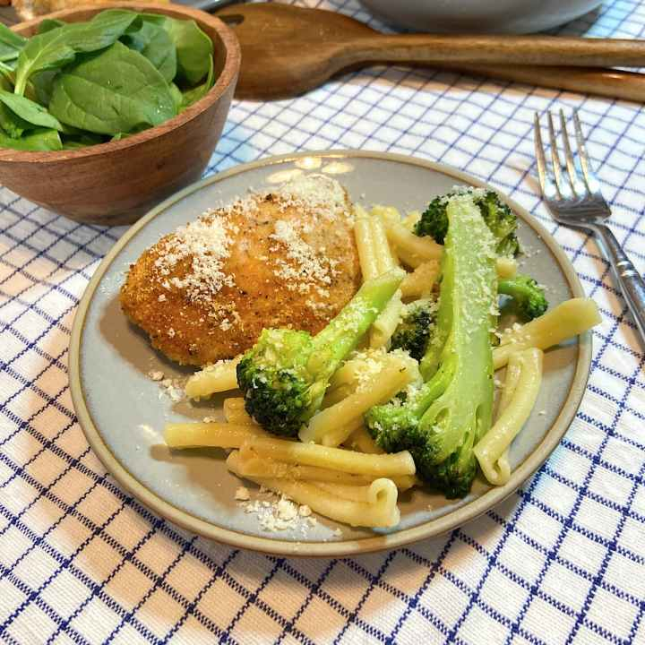pasta and broccoli on plate with parmesan cheese