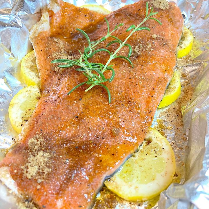 Salmon filet with lemon, olive oil, and spice rub on foil ready to bake.