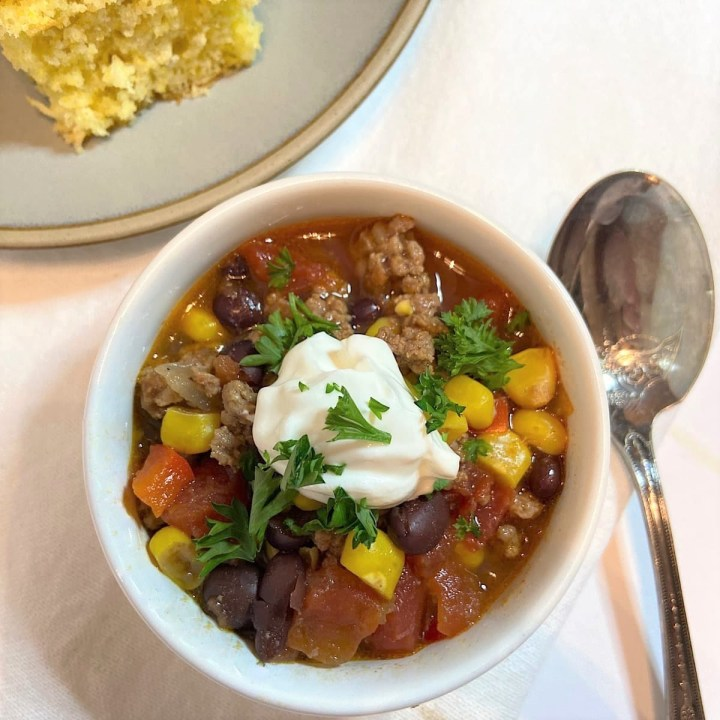 corn, black bean, beef chili in bowl with dollop of Greek yogurt