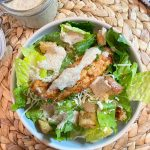 grilled chicken caesar salad with mayfair dressing in bowl
