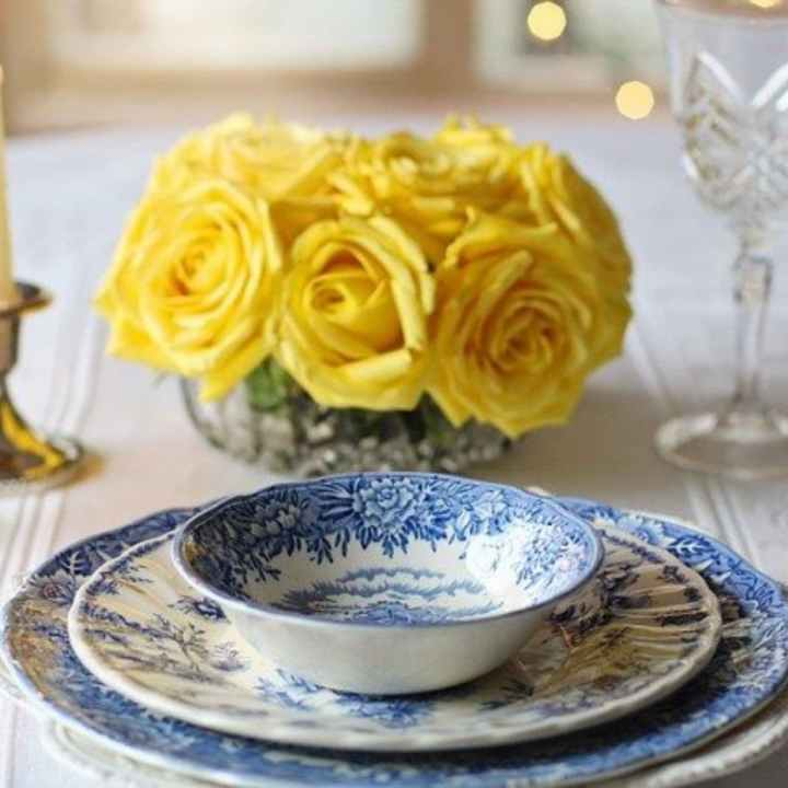 blue transferware dishes on table with stemware.
