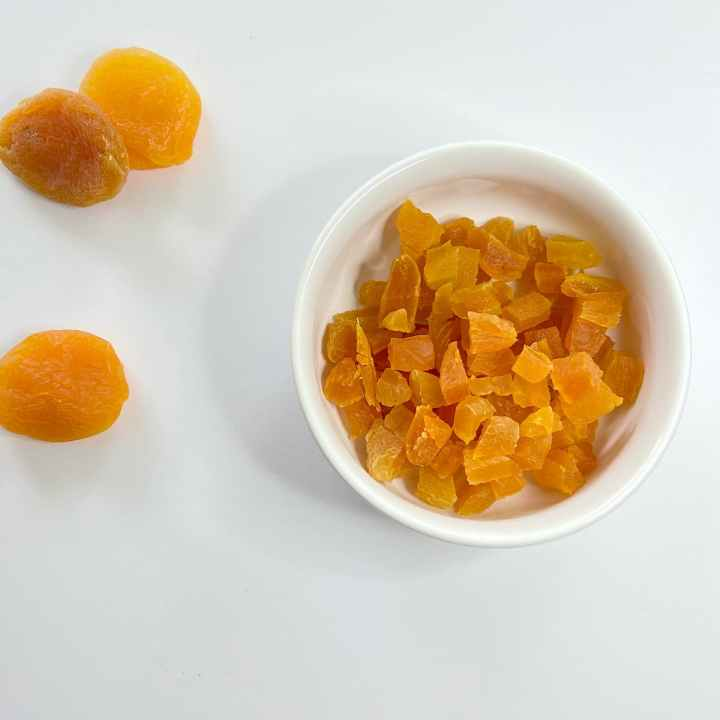 chopped dried apricots in a bowl next to 3 whole apricots