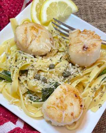 pan seared scallops with capers spinch and a lemon broth sauce on a plate.