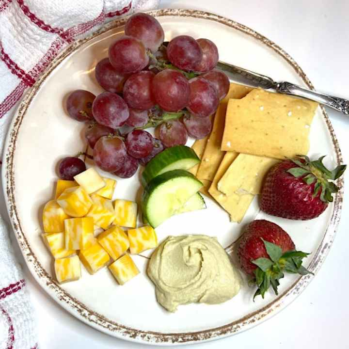 fruit, cheese, vegetables, crackers and hummus on plate
